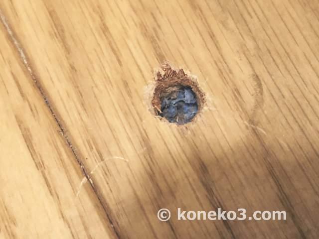 床に空いたビス穴の補修作業